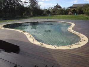 Black safety net on pool with large timber deck