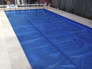 Solar blanket with C-Frame roller on rectangular pool